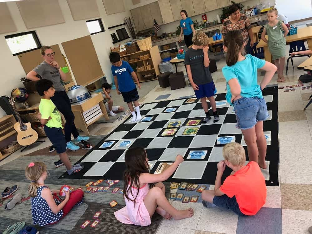 Kids playing giant coding game on floor mat